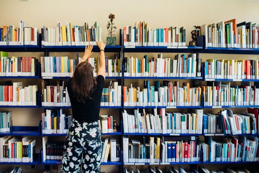 la bibliotecaria dispone dei libri sugli scaffali della biblioteca presente in sala studio