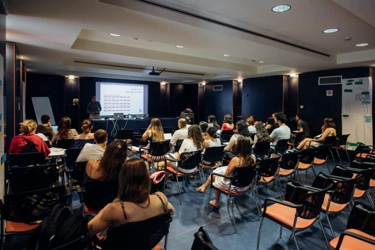 gruppo di studentesse e studenti seduti su sedie ascoltano il professore mentre spiega