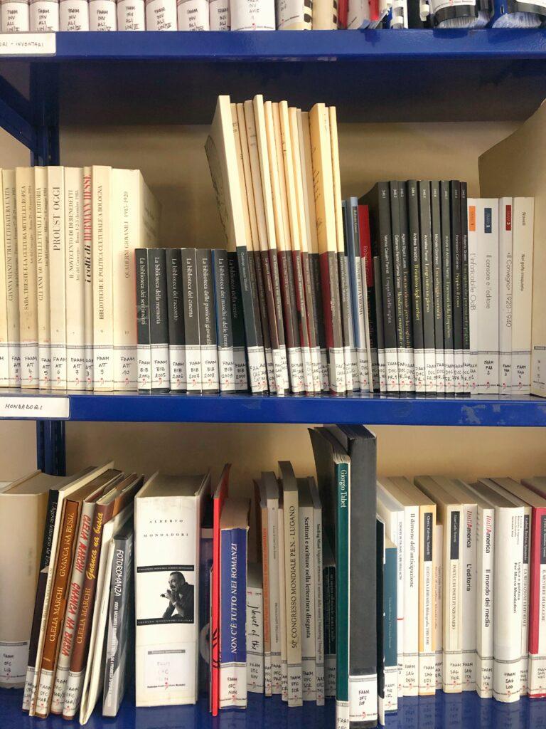 scaffale con i libri delle collane pubblicate da fondazione mondadori